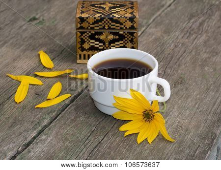Casket, Petals, Yellow Flower And Coffee, On A Wooden Table, A Still Life