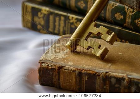 Antique Brass Key With Antique Books. Concept Of The Key Of Knowledge