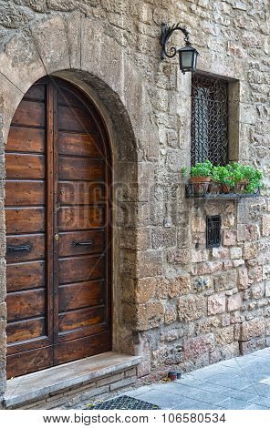Old Stone Wall Of The House With A Wooden Door, A Lamp And A Window