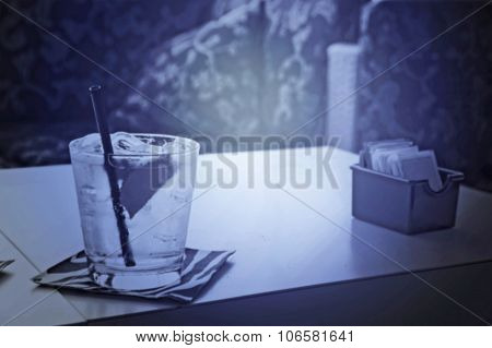 A Sun Lit Ice Cold Glass Of Water Or Cocktail With Ice And Lemon On A Table In A Dark Room, Artistic