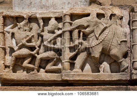 Carved In Stone Indian Elephant And The People On The Ruined Bas-relief On The Wall Of The Temple
