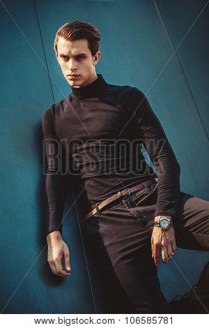 Man model in strict black dress near modern architectural environment.
