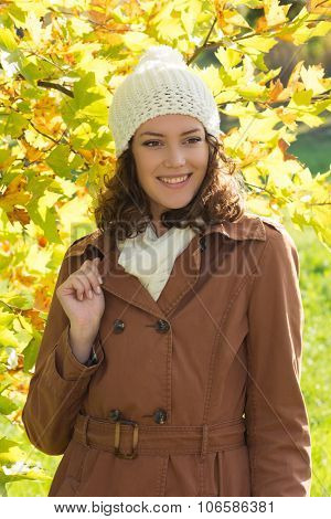 Young woman posing in a coat and with a cap in the front of yellow leaves