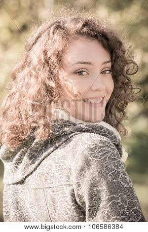 Close-up portrait of a beautiful young woman with curly hair