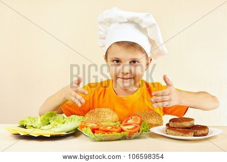Little boy in chef hat at table with ingredients for hamburger