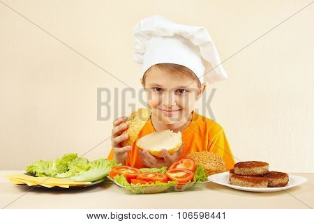 Little funny chef at the table with ingredients is going to cook hamburger