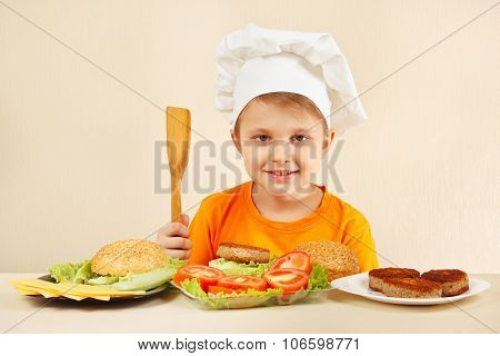 Young smiling chef at the table with ingredients is going to cook hamburger