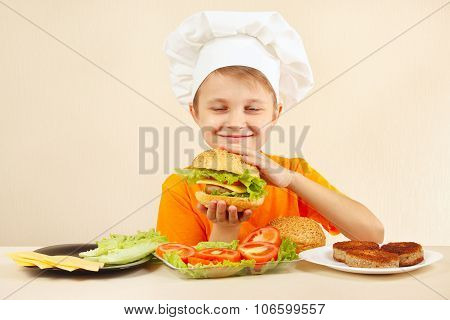 Little funny chef in chefs hat enjoys cooking tasty hamburger
