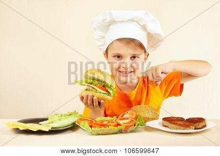 Little boy in chefs hat expressive enjoys cooked hamburger
