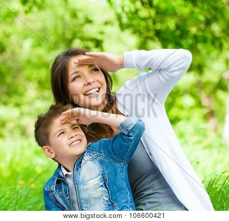 Mother and her son with book sitting on green grass cover eyes from sun in park. Concept of happy family relations and carefree leisure time