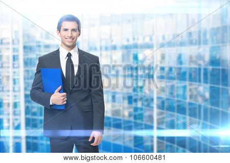 Portrait of businessman handing blue folder, modern background. Concept of leadership and success