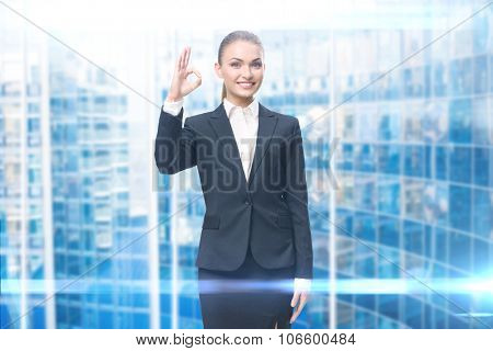 Portrait of businesswoman okay gesturing, blue background. Concept of leadership and success