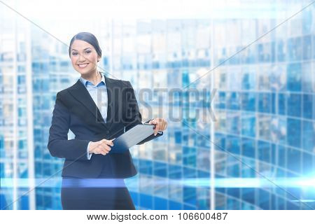 Portrait of businesswoman with black folder, blue background. Concept of leadership and success