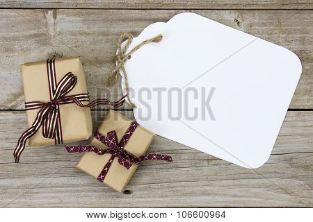 Large gift tag by presents on wood table