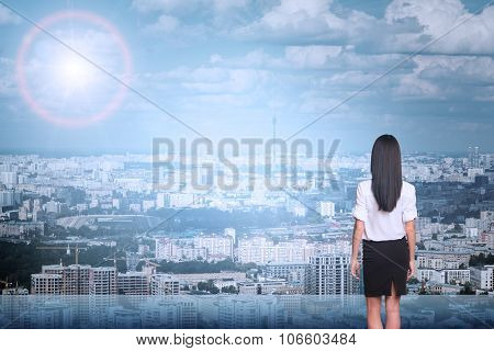 Businesslady on cityscape background, rear view