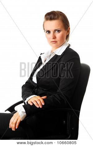 Portrait of serious modern business woman sitting on office chair