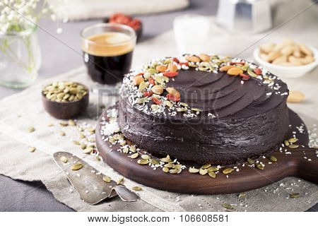 Vegan chocolate beet cake with avocado frosting, decorated nuts, seeds