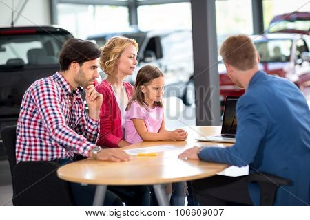 Family  interested in purchasing new car listens car agent in car showroom