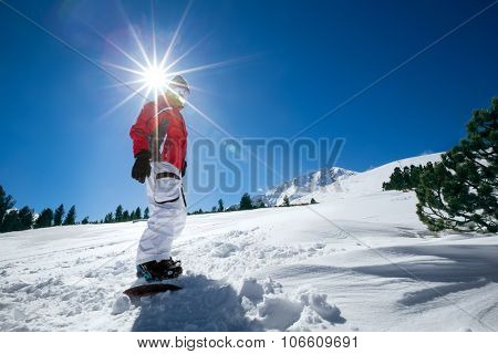 Snowboarder standing on snowboard over sunny sky