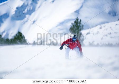Man snowboarding down hill in a snow powder