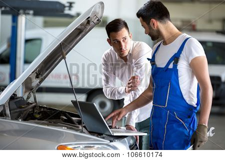 mechanic working on laptop computer with customer
