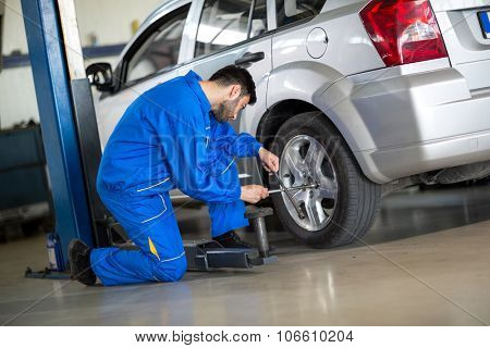 Mechanic change tyre on car