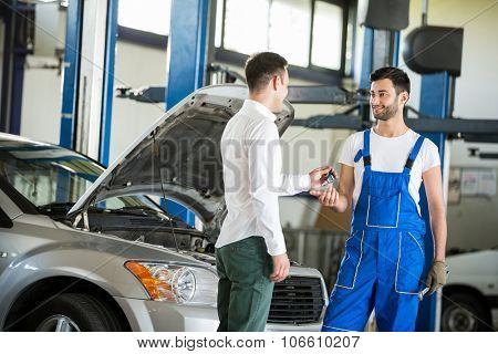 Customer giving him car keys to mechanic in service