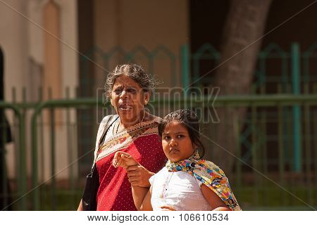 Little India, Singapore - 2008. Old Indian Woman With Her Granddaughter On The Street .