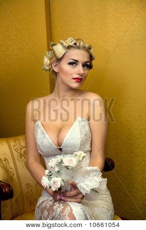 Bride Blond With A Bouquet Sits On A Chair