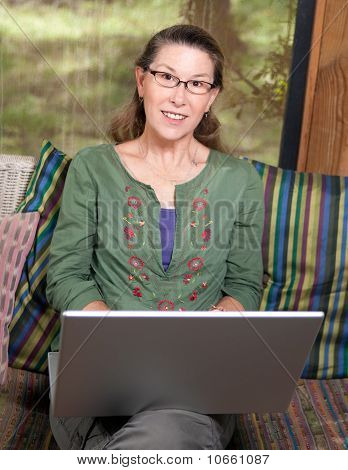 Mature Woman Portrait At Her Laptop Computer