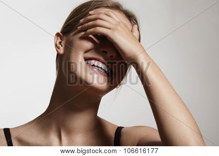 Woman In Braces Is Laughing And Close Her Eyes With A Hand