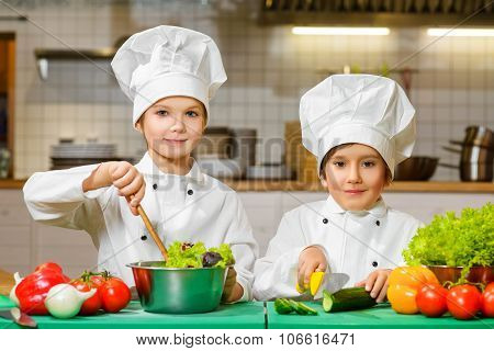Funny happy chef boys cooking at restaurant kitchen. concept of vegetarianism
