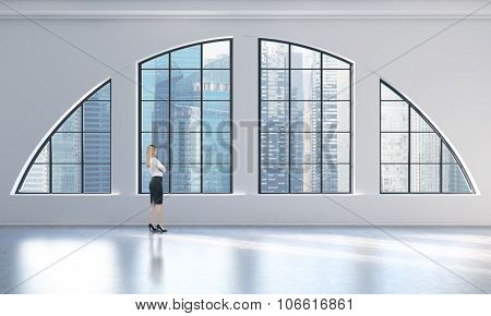 Rear View Of A Woman In Formal Clothes Who Is Looking Out The Window In A Modern Loft Interior. Sing