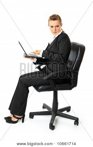 Displeased modern business woman sitting on chair and holding laptop in hand
