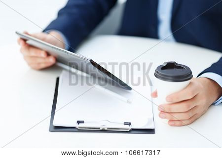 Office worker with tablet and papercup of coffee.