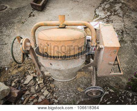 An orange Cement Mixer on the floor
