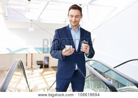 White collar worker glances at his smartphone.