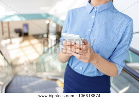 Corporate worker is using her smartphone.