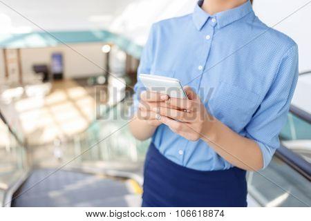 Corporate worker is using her smartphone.