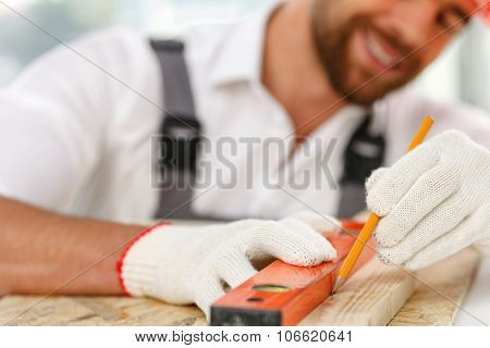 Attractive male carpenter is taking measurements of material
