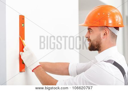 Attractive male carpenter is taking some measurements