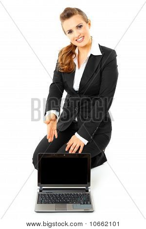 Smiling modern business woman sitting on floor and pointing on laptops blank screen