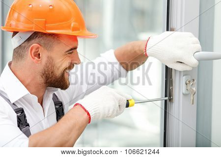 Cheerful male repairman is working with joy