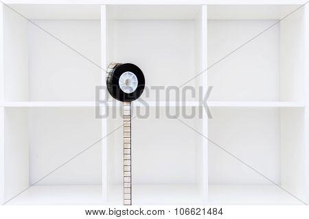 35 Mm Film Reel And Filmstrip On White Bookshelf