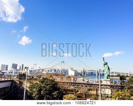 Lady liberty juxtaposed stand against Rainbow Bridge in Tokyo, Odaiba in Japan