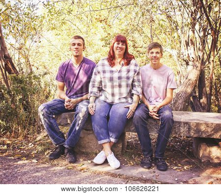 a cute family posing for a photo in a park setting with trees in the background toned with a retro vintage instagram filter effect app or action