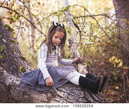 a cute girl sitting on a log in a thicket of trees toned with a retro vintage instagram filter effect app or action