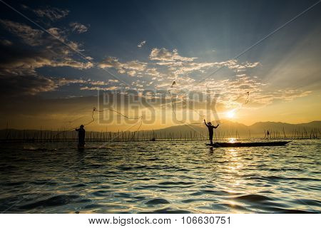 Silhouettes Of The Traditional Fishermen Throwing Fishing Net During Sunrise, Thailand