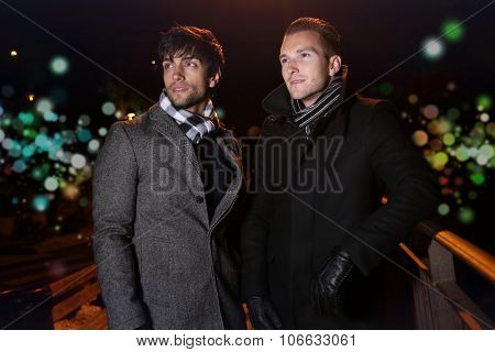 two elegant men posing during the night