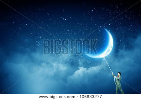 Young businessman in hat who obtains  moon with rope